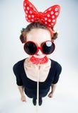 Ragazza sveglia con una grande lecca-lecca rossa e gli occhiali da sole divertenti Fotografia Stock