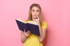 Ragazza sveglia confusa che pensa e che legge il libro sul fondo rosa variopinto Immagini Stock Libere da Diritti