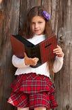 Ragazza sveglia contro la rete fissa di legno con il libro Immagini Stock