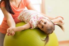 Ragazza sveglia del bambino che allunga sulla palla di forma fisica dei pilates con la mamma in palestra Immagine Stock