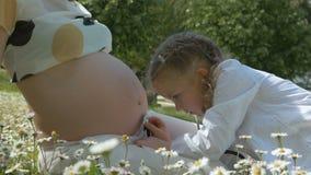 Ragazza sveglia del bambino che esamina la pancia incinta della madre video d archivio