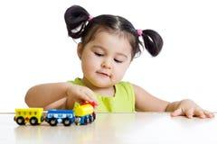 Ragazza sveglia del bambino che gioca i treni Fotografie Stock