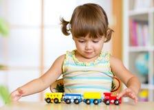 Ragazza sveglia del bambino che gioca il giocattolo di legno dei treni Immagine Stock