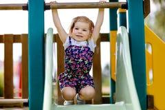 Ragazza sveglia del bambino che gioca sullo scorrevole sul campo da giuoco all'aperto Il bello bambino in variopinto mette i pant fotografie stock