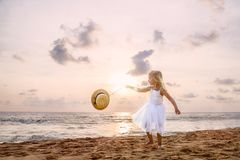 Ragazza sveglia del bambino con capelli biondi in un vestito ed in un cappello bianchi dal tutu che cammina su una spiaggia sabbi fotografia stock libera da diritti