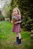 Ragazza sveglia del bambino con il canestro delle campanule nel giardino di primavera Fotografia Stock