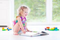 Ragazza sveglia del bambino con il libro di lettura biondo dei capelli ricci Fotografia Stock Libera da Diritti