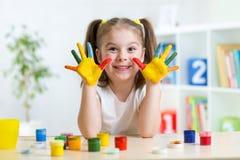Ragazza sveglia del bambino con le mani dipinte in variopinto fotografia stock
