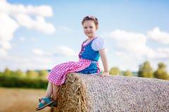 Ragazza sveglia del bambino in costume bavarese tradizionale nel giacimento di grano Immagine Stock Libera da Diritti