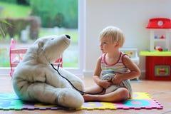 Ragazza sveglia del bambino in età prescolare che gioca al dottore gioco con i suoi giocattoli Fotografie Stock Libere da Diritti