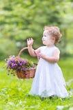 Ragazza sveglia del bambino nel giardino con il canestro del fiore Fotografia Stock