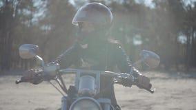 Ragazza sveglia del ritratto che indossa casco nero che si siede sul distogliere lo sguardo del motociclo Hobby, viaggiare e stil stock footage