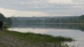 Ragazza sveglia del teenag che pesca sulla sponda del fiume che sta sulla sabbia e che tiene canna da pesca video d archivio