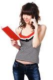 Ragazza sveglia dell'allievo con un libro rosso Fotografia Stock