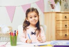 Ragazza sveglia della lettiera che dipinge o che fa il suo compito nella sua stanza Fotografie Stock