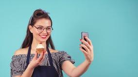 Ragazza sveglia della pasticceria che fa selfie con il bign? a disposizione archivi video