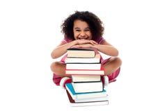 Ragazza sveglia della scuola che pende sopra la pila di libri Fotografia Stock