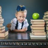 Ragazza sveglia della scuola che si siede alla tavola con molti libri Fotografia Stock