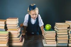 Ragazza sveglia della scuola che si siede alla tavola con molti libri Immagine Stock