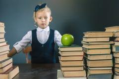 Ragazza sveglia della scuola che si siede alla tavola con molti libri Fotografia Stock Libera da Diritti