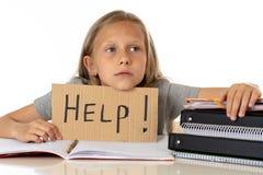 Ragazza sveglia della scuola dei capelli biondi che tiene un aiuto per firmare dentro un concetto di istruzione Fotografie Stock