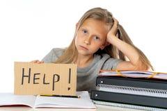 Ragazza sveglia della scuola dei capelli biondi che tiene un aiuto per firmare dentro un concetto di istruzione Immagini Stock Libere da Diritti