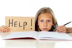 Ragazza sveglia della scuola dei capelli biondi che tiene un aiuto per firmare dentro un concetto di istruzione Fotografie Stock Libere da Diritti