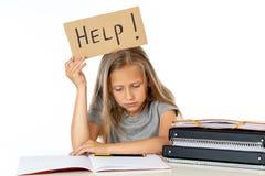 Ragazza sveglia della scuola dei capelli biondi che tiene un aiuto per firmare dentro un concetto di istruzione Immagine Stock