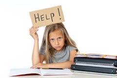 Ragazza sveglia della scuola dei capelli biondi che tiene un aiuto per firmare dentro un concetto di istruzione Immagini Stock