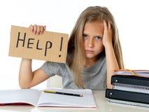 Ragazza sveglia della scuola dei capelli biondi che tiene un aiuto per firmare dentro un'istruzione Fotografie Stock Libere da Diritti