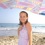 Ragazza sveglia della spiaggia sotto l'ombrello Immagini Stock