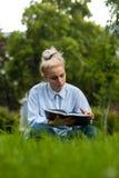 Ragazza sveglia dello studente che legge un libro sull'erba verde Immagine Stock