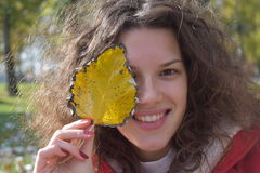 Ragazza sveglia di autunno con la foglia gialla Fotografie Stock Libere da Diritti