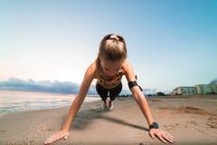Ragazza sveglia di misura che fa esercizio della plancia sulla spiaggia all'alba Immagini Stock Libere da Diritti