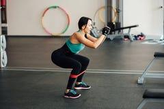 Ragazza sveglia di misura che fa gli esercizi di gamba Immagine Stock