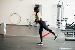 Ragazza sveglia di misura che fa gli esercizi di gamba Immagini Stock