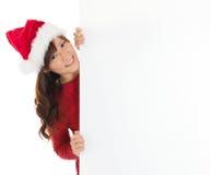 Ragazza sveglia di Santa che dà una occhiata da dietro il segno in bianco Immagini Stock