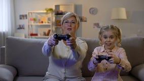 Ragazza sveglia e nonna moderna che giocano video gioco a casa con le leve di comando, svago archivi video