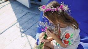 Ragazza sveglia felice che riposa ai fiori della barra di baia, di fiuto e sorridere lentamente archivi video