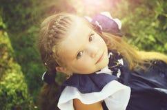 Ragazza sveglia felice con i capelli della treccia che sorride sull'erba verde immagini stock