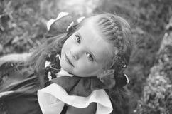 Ragazza sveglia felice con i capelli della treccia che sorride sull'erba verde immagine stock libera da diritti