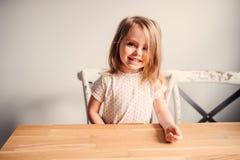 Ragazza sveglia felice del bambino che gioca nella cucina Fotografia Stock