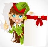 Ragazza sveglia l'elfo di natale con una bandiera Fotografia Stock