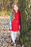 Ragazza sveglia nei supporti rossi del vestito accanto al grande albero immagini stock