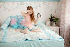 Ragazza sveglia nella camera da letto dei bambini piacevoli con la sveglia Fotografia Stock