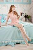 Ragazza sveglia nella camera da letto dei bambini piacevoli con la sveglia Immagini Stock Libere da Diritti
