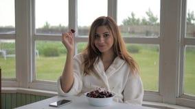 Ragazza sveglia nelle camice, sedentesi sulla veranda e mangianti ciliegia Fotografia Stock
