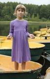 Ragazza sveglia otto anni che si levano in piedi sulla barca Fotografia Stock