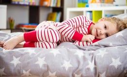 Ragazza sveglia in pigiama che dorme a letto Immagini Stock