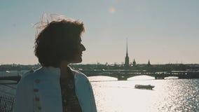 Ragazza sveglia in rivestimento bianco sul tetto con la vista scenica del fiume della città video d archivio